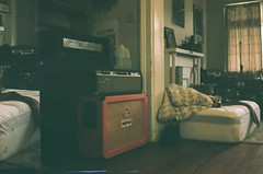 Pudge gear, my bed, front room of Heaven's Gate (emily_quirk) Tags: film emilyquirk 35mm nikon olympus nashville neworleans staypoorshootfilm filmsnotdead heavensgate showspace showhouse diy noladiy amps orange orangeamps pudge pudgegear endofanera era
