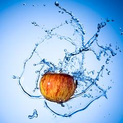 Apple Splash (Graham Scarborough) Tags: blue red food motion apple wet water fruit studio bright action ripple explosion wave fresh spray swirl flowing splash liquid foodanddrink freshness ripe refreshment splashing flickraward5
