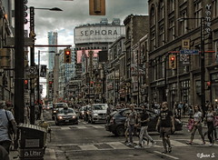 Crossing (Jean S..) Tags: toronto street people light sky clouds grey red streetphoto candid cars rain rainy lines