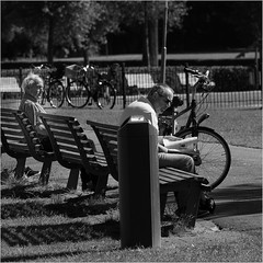 A watchful eye (John Riper) Tags: johnriper street photography straatfotografie rotterdam square bw black white zwartwit mono monochrome netherlands candid john riper canon 6d 24105 l people men grass bikes bicycles kralingse bos watch bench dustbin reading magazine