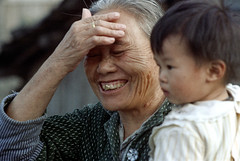 33-207 (ndpa / s. lundeen, archivist) Tags: nick dewolf nickdewolf color photographbynickdewolf 1970s 1972 fall film 35mm winter republicofchina taiwan taiwanese china chinese 1973 people woman oldwoman face smile smiling goldtooth hold holding carry carrying child boy womanandchild 33 reel33