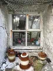 Interesting window, coffee anyone? (mootzie) Tags: coffeepots frames quaint whitewash weeds sugarpot rustynails reflectiongrass whitewoodenwindowpanescoffeepotsnettingflowershouseblacklewisscotland