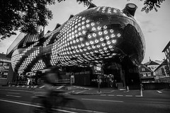 The fast Biker (Norbert Eder) Tags: street light blackandwhite white black building art monochrome architecture night lights sony streetphotography kunsthaus 12mm graz walimex steiermark a6000 sterrech