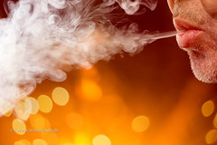 male mouth is blowing smoke out, with bokeh background (Armin Staudt) Tags: man black blur macro male closeup mouth studio technology hand cigarette background smoke blowing lips smoking safe cigarettes smoker quit vapor nicotine vaporizer exhaling inhaling vaping