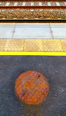Waiting/Seeing Symmetry (stephenbryan825) Tags: huyton liverpool robystation abstracts balanced central equality graphic manholecover rails selects station symmetrical vivid yellow