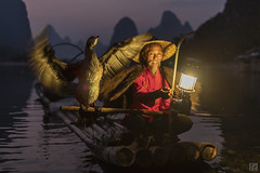 Wings at Dusk (lycheng99) Tags: china travel sunset red sky motion mountains lamp reflections river cormorants lights liriver flying wings fisherman dusk guilin gaslamp cormorant raft redsky pinksky karst guangxi bambooraft cormorantfishing xingping cormorantfisherman ljing karstformation
