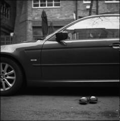 Nike and Her Chariot (David Stumpp |[o]| Photography) Tags: oxford england unitedkingdom uk greatbritain oxon oxfordshire blackandwhite bw monochrome film mediumformat ilford delta400 120 400 tmax dev rolleiflex 28f tlr twinlensreflex 6x6 square daylight natural available light outdoors lighting portrait old oldshoes shoes sandals slipon nike bmw abandoned car automobile side pavement street asphalt waiting empty wwwdavidstumppcom nikeandherchariot blue boar fpp