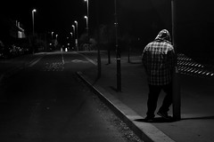 alone in the light (jakeskitt) Tags: night street portrait black white photography staged light gloucester moody lamp bridge road lonely alone hoodie leaning nikon late tripod long exposure checked shirt lens flare