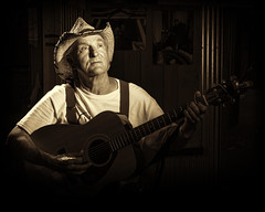 Randy and His Guitar (TNrick) Tags: ohio portrait man monochrome sepia grid cowboy guitar cincinnati cowboyhat lowkey oldconey appalachianfestival topazyn560iii