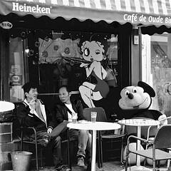 IF MINNIE WOULD KNOW.... (Akbar Simonse) Tags: dscn3301 rotterdam rotjeknor holland netherlands nederland streetphotography straatfotografie people candid terras cafe bar sitting bettyboob heineken bier beer mickeymouse mannen men zwartwit bw bn monochrome vierkant square akbarsimonse