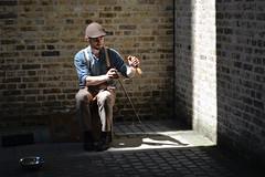 Man busks with saw instrument (Josh6001) Tags: people busker bricks saw instrument music money shadow hat wall london uk unitedkingdom nikon d5200 streetphotography