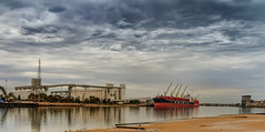 Loading from the silos. (johnwilliamson4) Tags: adelaide cementworks clouds conveyors cranes industrial panorama pylons ship silos southaustralia transportation water reflections australia