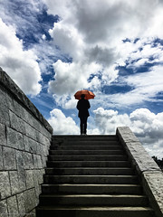 weathering heights (bluechameleon) Tags: sky woman color colour apple silhouette clouds stairs umbrella seawall figure westend cloudporn iphone bluechameleon orangeumbrella sharonwish bluechameleonphotography iphone6s