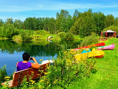 My sister, Judy, relaxing here on Bluebird Estates (peggyhr) Tags: peggyhr bench lake boats canoes dock gazebo forest reflections blue green yellow red purple hbm bluebirdestates alberta canada