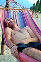 Colorful Hammock (Christina 25) Tags: beach outdoors man laugh colours enjoyment smile holidays hammock swing swimsuit seesaw sand person macedonia makedonia macedoniatimeless greece joy happiness naked joke