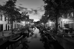 Light on the water (McQuaide Photography) Tags: haarlem noordholland northholland netherlands nederland holland dutch europe sony a7rii ilce7rm2 alpha mirrorless 1635mm sonyzeiss zeiss variotessar fullframe mcquaidephotography captureone phaseone c1 captureonepro9 tripod manfrotto light licht lowlight night nacht nightphotography architecture outdoor outside water reflection gebouw building calm peaceful tranquil atmosphere still wideangle wideanglelens groothoek blackandwhite bw blackwhite mono monochrome canal city stad house huis huizen residential bakenessergracht gracht old oud oldhouse oldbuildings longexposure