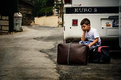 The saddest happy escape (Melissa Maples) Tags: ibrad turkey trkiye asia  nikon d5100   nikkor afs 18200mm f3556g 18200mmf3556g vr ormana coach bus road street turk child boy bags baggage luggage suitcases