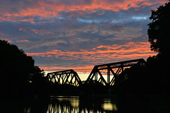 Sunset Over Erie Canal (dr_marvel) Tags: sunset clouds red blue evening canal erie eriecanal pittsford ny newyork bridge railroad train water waterway