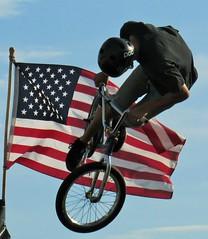 Stunt bike (Rose*Bud) Tags: bike stunt flight flag summer boardwalk air