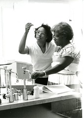 Two women work on an experiment (A) (PUC Special Collections) Tags: laboratory lab pacificunioncollege chemistrydepartment chemistrylab chemistry beakers test tubes scientist labcoat experiments angwin california adventist sda seventhdayadventist college