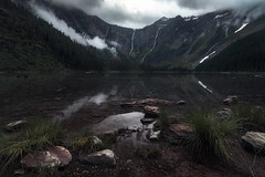Dark Atomosphere (sharpedit) Tags: natural causes avalanche lake glacier national park montana landscape clouds mountain snow waterfall gray reflection
