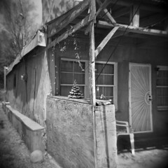 Christmas Comes to Cerrillos (LowerDarnley) Tags: holga cerillos newmexico house christmas christmastree adobe lights festive christmasinapril