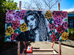 Wine and Roses (Steve Taylor (Photography)) Tags: amywinehouse miriamhansen easel roses sandbag art painting portrait streetart stencil aerosol paint spray canvas woman lady newzealand nz southisland flower rose spring sunny sunshine nelson