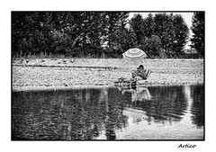 Relaxing by the river (Artico7) Tags: river water clear clean rocks stones relax relaxing quiet leisure sun hot summer woman umbrella trees tagliamento friuli italy bw blackwhite blackandwhite biancoeenero monochrome fuji xe1 reading magazine feet stripes fresh refreshing