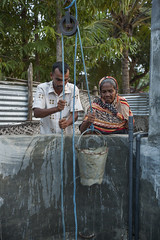 Drawing from the well 6564 (shahidul001) Tags: people man male woman female elderly old aged srilankan srilankans water bucket rope nylonrope pulley well rural village life dailylife vertical color colour srilanka southasia asia drik drikimages