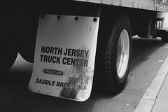 North Jersey Truck Center (Greyframe) Tags: street new city shadow urban bw usa white newyork black monochrome wheel sign contrast truck photography grey blackwhite moving newjersey outdoor walk side move rubber company dirt cover jersey load weiss schwarz freight saddle movers blwh freightliner schwarzweis greyframe