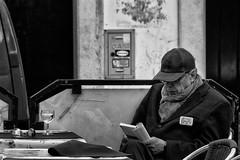 'Vinho Verde and Rhino' (Canadapt) Tags: man elder reading glass wine table cap sitting seated rhino emblem alfama portugal bw canadapt street sunglasses
