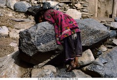 AAEC001347 (ngao5) Tags: people afghanistan girl rock female reading one clothing asia child dirty barefoot resting tiredness centralasia exhausted oneperson jalalabad afghani everydayscene nangarharprovince poorperson easternasian asianandindianethnicities centralasianculture centralasianethnicity