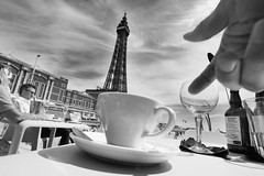 Cappuccino, Sun & a Tower (Idreamofpies) Tags: blackpool uk britain lancashire seafront promenade cafe beach hut tower coast seaside gand cup saucer towe sky clouds monochrome balckandwhite table chilling idreamifpiesphotography