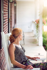 (Rebecca812) Tags: woman porch rockingchair redhair ginger curlyhair ponytail lookingaway sundress atmospheric portrait vertical storytelling brick frontporch house home summer flower rebecca812 canon canon5dmarkii