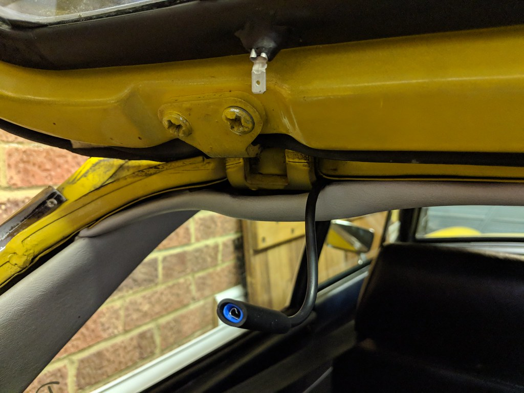 Wire with spade connector emerging from under headlining ready to attach to matching connector embedded in rubber rear window surround